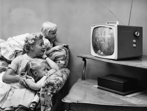 1955 - family is watching television at home
