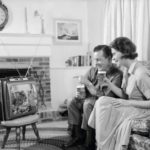 1960, a young couple is watching a portable TV in the living room
