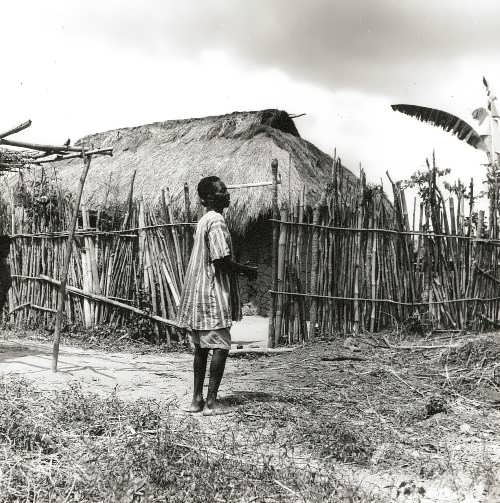 The village is in the savannah. A local resident near a fenced hut