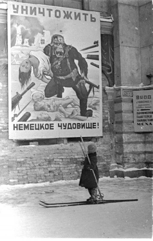 A child in the street of besieged Leningrad at the poster Destroy the German monster!. Winter 1941-1942