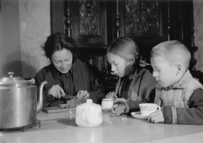 Music teacher Nina Mikhailovna Nikitina and her children Misha and Natasha share the blockade ration, February 1942