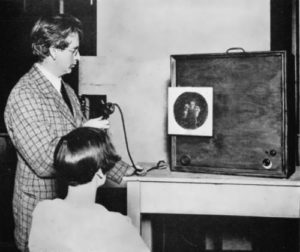 John Logue Baird in front of the screen of one of the first television transmitters
