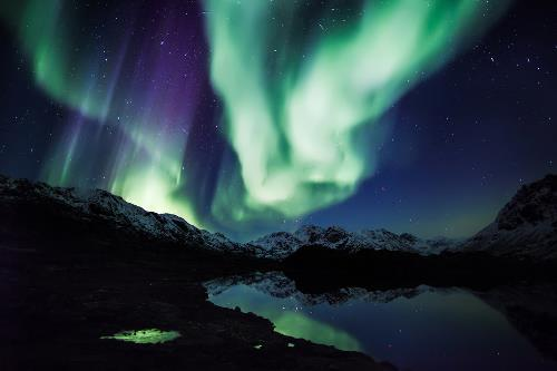Northern lights over the mountains and the lake. Photo by Mads Pihl