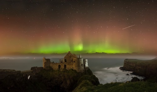 Northern lights over the ruins of a medieval Dunluce Castle