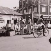 Cyclist rides past street vendors