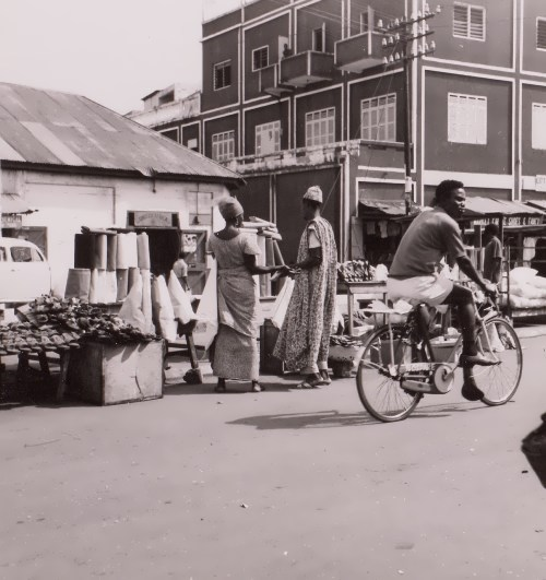 Cyclist rides past street vendors