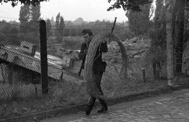 The soldier is carrying a large roll of barbed wire, August 21, 1961