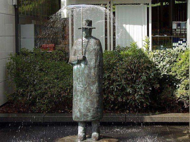 Fountain Man with umbrella in Lausanne, Switzerland